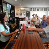 BRYAN EATON/Staff Photo. Bartender Emilee Elliott oversees her regular customers.