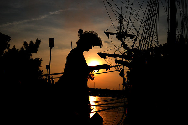 JIM VAIKNORAS/Staff photo A man dressed as a pirate boards as the sun sets behind El Galeon as it rest along the Newburyport waterrfront in the Merrimack River.