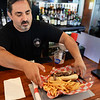 BRYAN EATON/Staff Photo. Bartender Tony Kataxinos delivers a steak and cheese grinder to a customer.