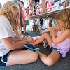 JIM VAIKNORAS/Staff photo Employee Abby Angelosanto helps Samantha Morris, 8 of Newburyport pick out sneakers at Hyman's Yankee Homecoming sale.