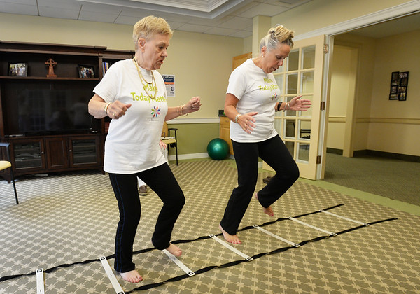 BRYAN EATON/Staff photo. Jill Ramsdell, right, with Patricia Busch on balance excercises along a ladder.