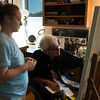 JIM VAIKNORAS/Staff photo Laura Cassen helps  Ron Emmerling as he paints at his Newburyport home.