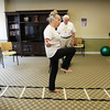 BRYAN EATON/Staff photo. Jill leads David Volckhausen on balance excercises along a ladder.