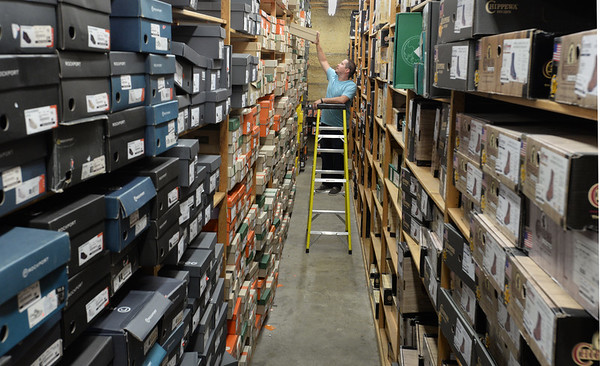 BRYAN EATON/Staff Photo. Brian Fuller who has been with Hyman's for 15 years retrieves a box of shoes in one of their large storage areas.