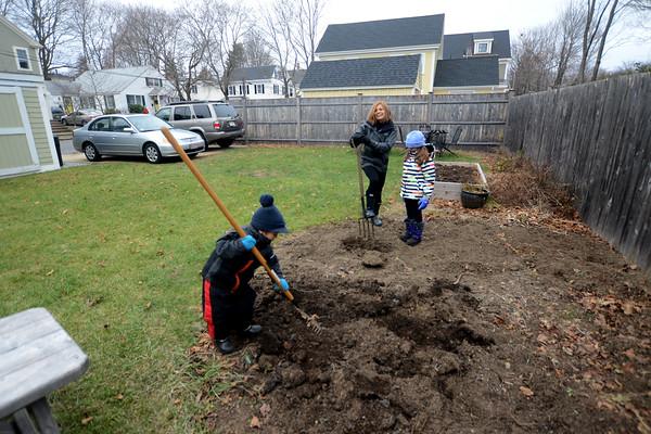 JIm Vaiknoras/Staff photo Dimitra Manesis and her kids Maia and Samuel  Manesis-Naylor tending their garden.