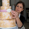 JIM VAIKNORAS/Staff photo Jenny Williamson adds a rose to one of her cakes at her bakery in Amesbury.