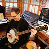 BRYAN EATON/Staff photo. EJ Ouellette is his sunroom, a banjo one of the instruments he plays.