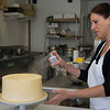 JIM VAIKNORAS/Staff photo Jenny Williamson sprays edible gold paint on one of her cakes at her bakery in Amesbury.