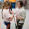 JIM VAIKNORAS/Staff photo Victoria Vigneaux, 11 and Izzy Leuasseur, 11, strap on harnesses at the Girls Rock Climb-A-Thon to benefit Girls Inc. of the Seacoast Area, a program of the Jeanne Geiger Crisis Center at Metro Rock Climbing in Newburyport.