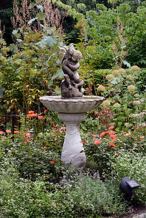 BRYAN EATON/Staff photo. A fountain that Doug and his late wife Donna purchased at Perennial Gardens in Newbury 25 years ago is surrounded by roses and other plants.