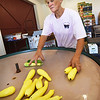 BRYAN EATON/Staff photo. Donna Bartlett collects summer squash to pack after being washed.