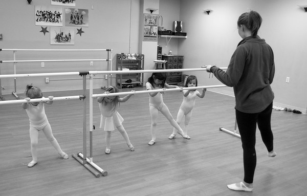 Abby Tanger teaches students degage on the bar.
