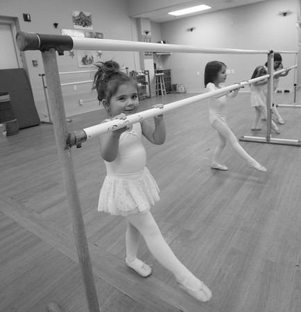 Angela Stanley and Anais Byron practice degage with the bar during their dance class.