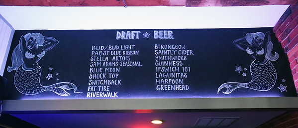 BRYAN EATON/Staff photo. Keeping with the nautical feel, mermaids adorn the beer selection board.