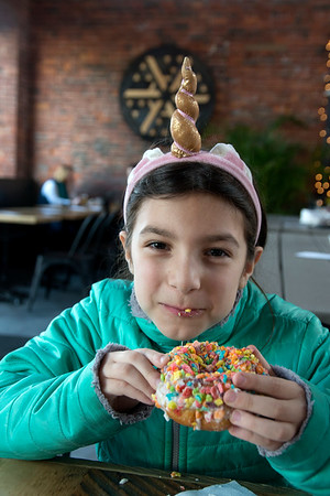 JIM VAIKNORAS/Staff photo Fabiana Deluca, 7, enjoys a Pebbles cereal donut from Angry Donut at Silvaticus in Amesbury. She is dressed as a unicorn.