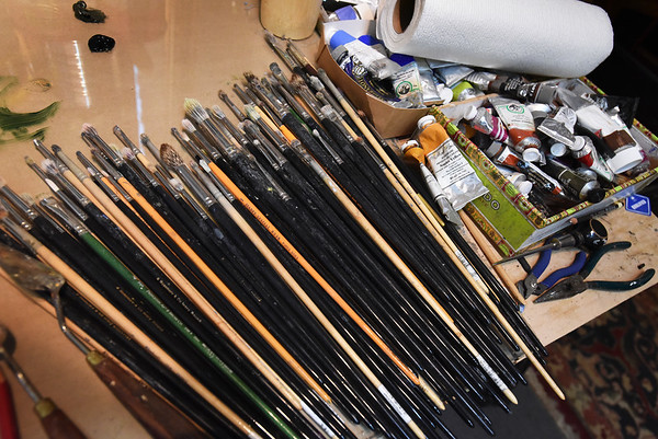 BRYAN EATON/Staff photo. Brushes and tubes of paint along with other implements cover Jurney's work bench.