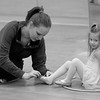 Abby Tanger helps Grace Pouliot with her ballet slippers.