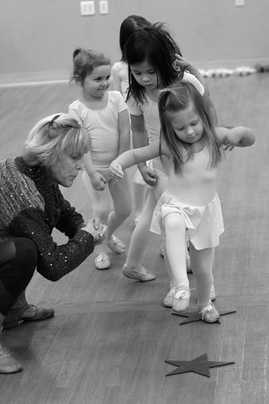 Teacher Cindy Conley helps Grace Pouliot with her balance during ballet class at the Broadway Dance Academy in Newburyport.