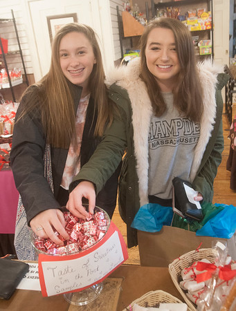 JIM VAIKNORAS/Staff photo Abby Maines, 15, and Kiara Ashe, 16, grab some chocolate at Simply Sweet on Inn Street in Newburyport. The store was one of many giving out treats as part the Sweet Taste of Newburyport.
