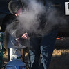 JIM VAIKNORAS/Staff photo Rick Rousseau of Mill River Winery makes mulled wine at the Old Newbury Christmas Tree Bonfire at the Tendercrop Farm fields and Spencer Perce-Little Farm in Newbury Saturday night. Ethan was their with his band Working it Out.