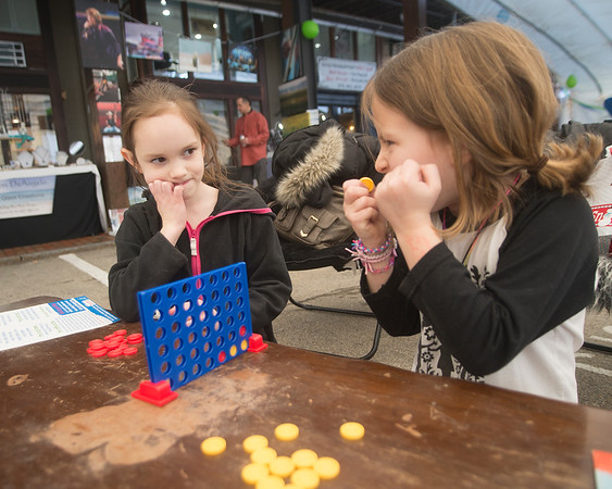 JIM VAIKNORAS/Staff photo Claire Strattner 8, and Charlie Santoro , 8, play Connect Four at the WE=NBPT festival at the Tannery in Newburyport Saturday.