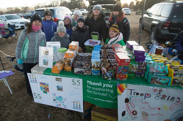JIM VAIKNORAS/Staff photo Girls from Scout Troop 88183 in Georgetown sell cookies at the Old Newbury Christmas Tree Bonfire at the Tendercrop Farm fields and Spencer Perce-Little Farm in Newbury Saturday night. Ethan was their with his band Working it Out.