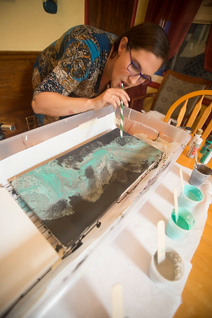 JIM VAIKNORAS/Staff photo Artist Melissa Wilkinson uses a straw to manipulate paint poured on a canvas.