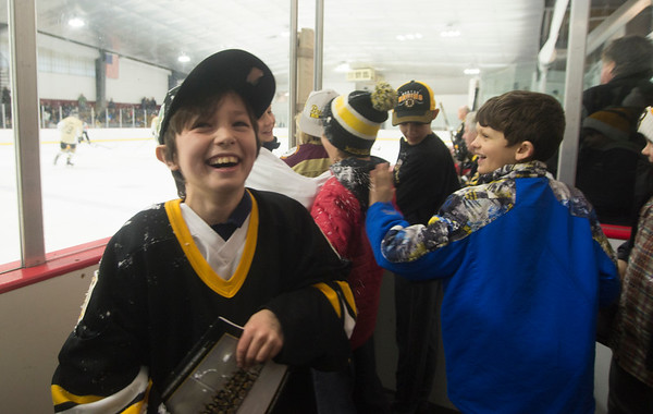 JIM VAIKNORAS/Staff photo Braedan Arel laughs after getting ice thrown on him by a Bruin's player Newburyport Youth Hockey's game against the Boston Bruin's Alumni team Saturday at the Graf Rink in Newburyport.