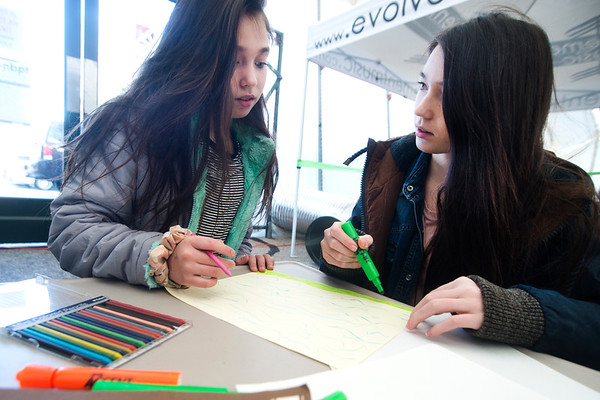 JIM VAIKNORAS/Staff photo Sisters Emily , 10, and Kalla, 12, Lively make use of the art supplies at the WE=NBPT festival at the Tannery in Newburyport Saturday.