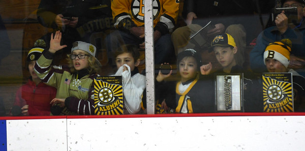 JIM VAIKNORAS/Staff photo Young fans watch through the glass at the Newburyport Youth Hockey's game against the Boston Bruin's Alumni team Saturday at the Graf Rink in Newburyport.
