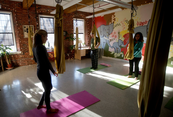 JIM VAIKNORAS/Staff photo Yoga instructor Carrie Schumacher works with George Stroman and Irene Sullivan  at the Sajni Center in Amesbury.