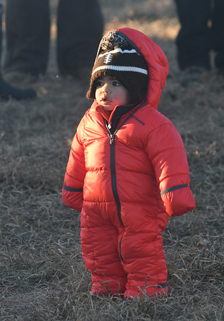 JIM VAIKNORAS/Staff photo Nathan Bisci-Friedman, 1, of West Newbury came bundled up for the cold at the Old Newbury Christmas Tree Bonfire at the Tendercrop Farm fields and Spencer Perce-Little Farm in Newbury Saturday night. Ethan was their with his band Working it Out.