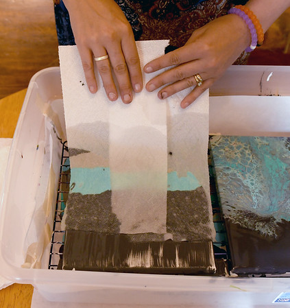 JIM VAIKNORAS/Staff photo Artist Melissa Wilkinson uses wet paper towels to spread paint over a canvas.