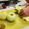 BRYAN EATON/Staff Photo.Jonathan Zinck prepares Granny Smith apples for baked turnovers, part of the Superbowl theme offerings.