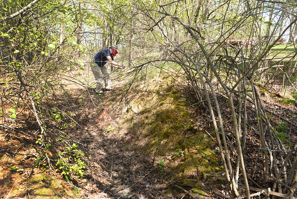 "BRYAN EATON/Staff photo. Newburyport history enthusiast Jack Santos looks at a mound next to a trench behind the Newburyport DPS yard searching for evidence of a ""pest house"" he thinks was in that location."