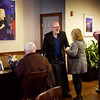 BRYAN EATON/Staff Photo. Loretta recently held a reception for local artist Alan Bull, center, with his work on the dining room wall.