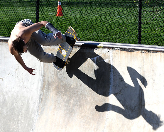 JIM VAIKNORAS/Staff photo Evan Boches casts a long shadow as he grinds the rim at Newburyport Skate Park.