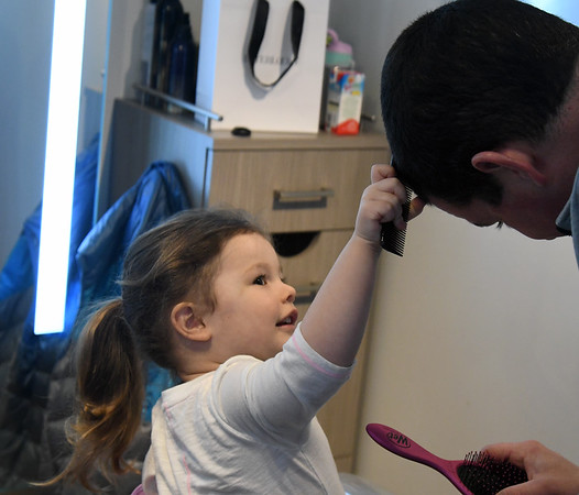 JIM VAIKNORAS/Staff photo Zoe Shoreman, 2, of Byfield combs her dad Sam's hair at daddy daughter hair styling at Interlocks.