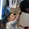JIM VAIKNORAS/Staff photo Zoe Shoreman, 2, of Byfield combs her dad Sam's hair at daddy daughter hair styling at Interlocks.