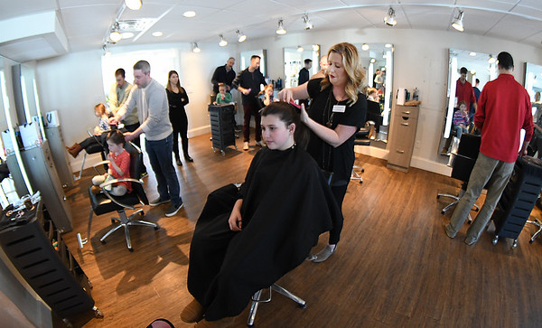 JIM VAIKNORAS/Staff photo Stylist Alisson Mchale demonstrates a pony tale with her daughter Grace, 11, at a daddy daughter hair styling at Interlocks in Newburyport.