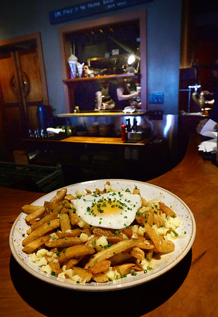 BRYAN EATON/Staff Photo. Poutine, which is french fries, gravy and cheese curds, here with the addition of a fried egg.