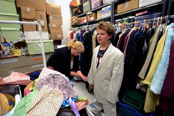 JIM VAIKNORAS/Staff photo Pamala McKenzie of the Theater Workshop hems Ryan Milligan's jacket  at Newbury Elementary School.