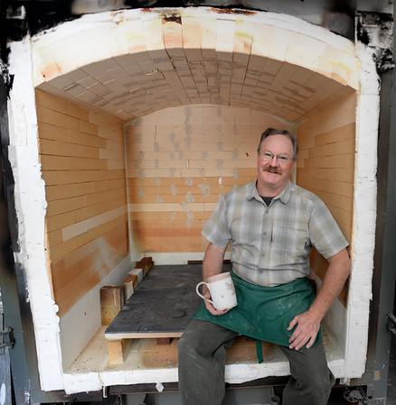 BRYAN EATON/Staff photo. Lloyd Hamovit of Two Rivers Ceramics poses inside one of his pottery kilns.