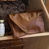 JIM VAIKNORAS/Staff photo Envelope clutch in brown leather at Vaalbara $198