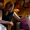"JIM VAIKNORAS/Staff photo Jen Collins with her cat Lilly in her home office sourounded by her late husband Ted's guitars. Jen has started a foundation ""Tedrock"" to riase money for music education."