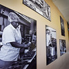 BRYAN EATON/Staff photo. Photos of the production line adorn the walls of the retail shop.