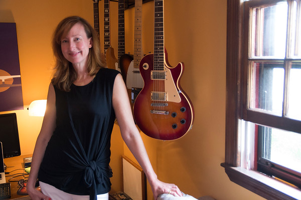 "JIM VAIKNORAS/Staff photo Jen Collins in her home office sourounded by her late husband Ted's guitars. Jen has started a foundation ""Tedrock"" to riase money for music education."