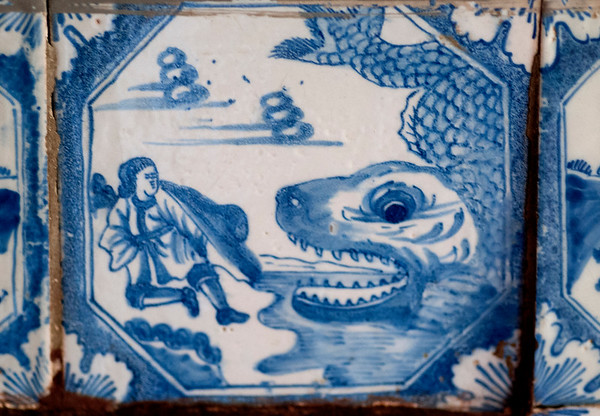 JIM VAIKNORAS/Staff photo A white tin glaze tile on clay depicting Jonah and the Whale, although in the biblical story it's a fish, is one of many sourounding the fire place in the Parlor at the Coffin House.