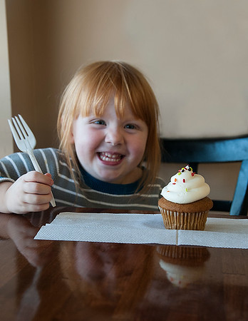 JIM VAIKNORAS/Staff photo Primrose Tervo, 3, who everyone calls Rosie, enjoys a banana cupcake at Dianne's Fine Desserts in Newburyport.