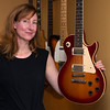 "JIM VAIKNORAS/Staff photo Jen Collins in her home office sourounded by her late husband Ted's guitars. Jen has started a foundation ""Tedrock"" to riase money for music education. She is holding a guitar she refers to as ""His Mistress"" which was giving to him by his father for his high school graduation.."